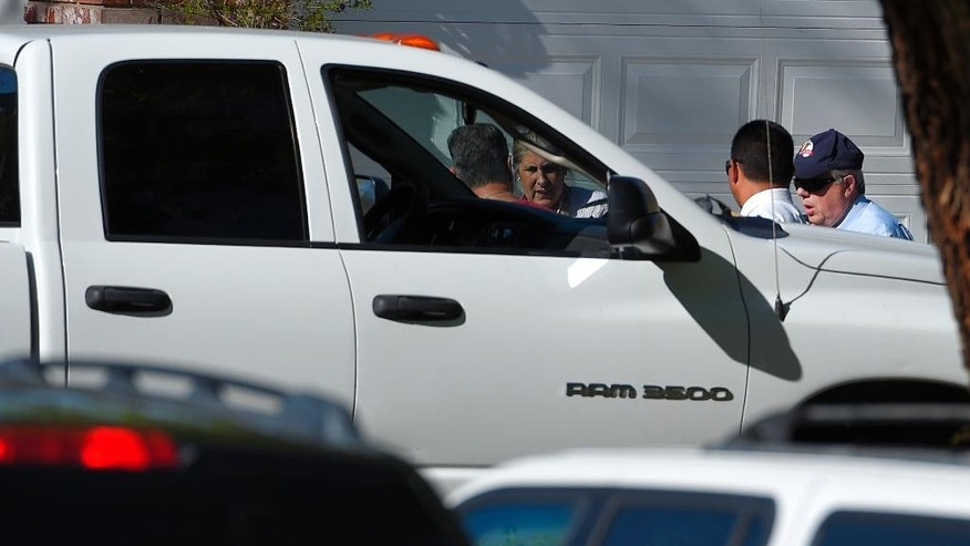 An off-duty Los Angeles police officer, left, talks to investigators next to his vehicle at the scene of an officer involved shooting, Sunday, March 29, 2015, in Santa Clarita, Calif. Authorities have detained a man suspected of shooting at an off-duty Los Angeles police officer from a car before fleeing the scene at a suburban neighborhood in northern Los Angeles county. (AP Photo/Mark J. Terrill)