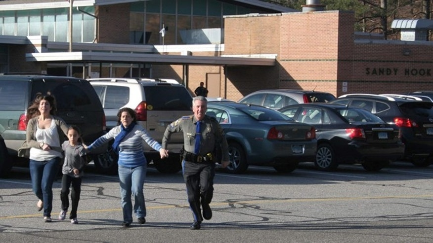 Dec. 14, 2012: In this file photo provided by the Newtown Bee, a police officer leads two women and a child from Sandy Hook Elementary School.