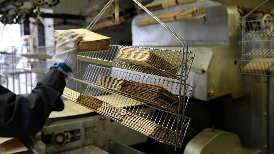 Matzos straight from the oven are loaded onto racks at the Streit's matzo factory in New York, Wednesday, March 4, 2015. (AP Photo/Seth Wenig)