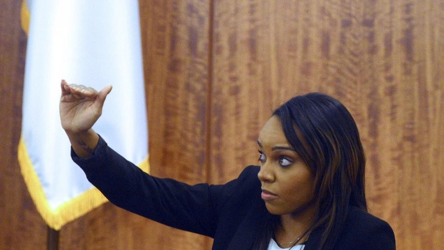 Shayanna Jenkins, fiancee of former NFL football player Aaron Hernandez, describes the size of a box as she testifies in court during Hernandez's murder trial, Monday, March 30, 2015, in Fall River, Mass. Jenkins testified that she removed a box from their basement at Hernandez's request the day after Odin Lloyd was found shot to death. (AP Photo/Boston Herald, Ted Fitzgerald, Pool)