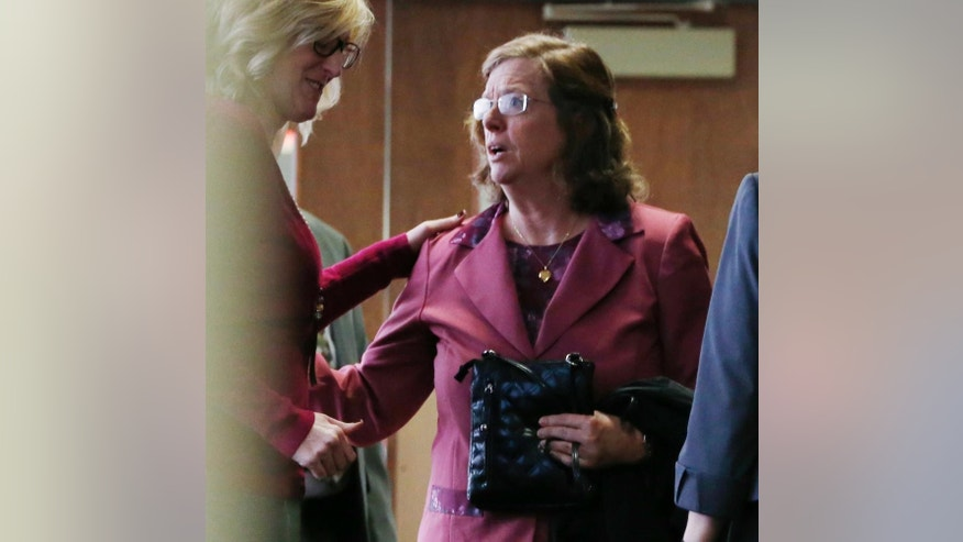 "File--In this file photograph taken on Monday, Dec. 8, 2014, an unidentified woman, left, consoles Arlene Holmes, right, as she leaves the courtroom after a pre-trial readiness hearing in Centennial, Colo., in the murder trial of her son, James Holmes, who is charged with killing 12 moviegoers and wounding 70 more in a shooting spree in a crowded theatre in Aurora, Colo., in July 2012. Arlene Holmes and her husband, Bob, told the Del Mar Times in the couple's first interview since the mass shooting about the book she wrote after her son's rampage in which she said that she prays for the victims of the theatre rampage daily ""by name and by wound.""  (AP Photo/David Zalubowski, File)"