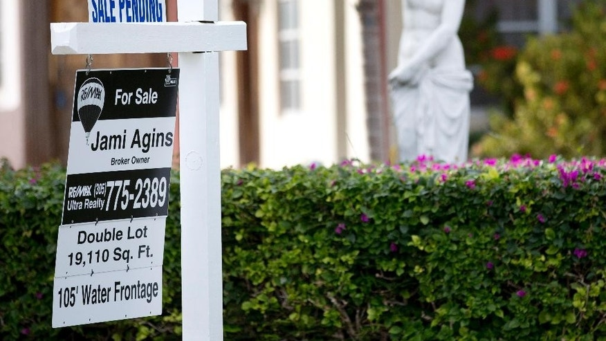 "In this Thursday, Jan. 8, 2015 photo, a ""sale pending"" placcard is placed atop a realty sign outside a home for sale in Surfside, Fla. More Americans signed contracts to buy homes in February, the National Association of Realtors reported Monday, March 30, 2015, evidence that the spring buying season could open strong after sluggish sales for much of the winter. (AP Photo/Wilfredo Lee)"