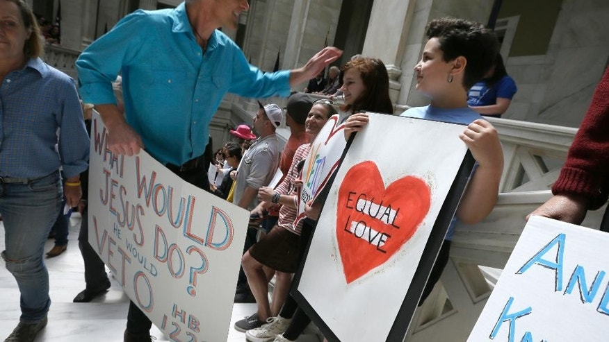 Protesters gather on the steps near the House chamber at the Arkansas state Capitol in Little Rock, Ark., Monday, March 30, 2015. A House committee earlier Monday advanced an amended version of a bill that opponents say allows discrimination against gays and lesbians. (AP Photo/Danny Johnston)
