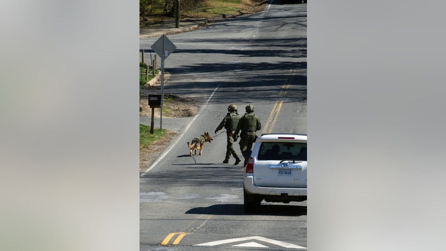 A FBI K-9 unit searches an area in Annandale, Va., Tuesday, March 31, 2015, near the Inova Fairfax Hospital for a prisoner who broke free from his security guard and took his gun at the hospital earlier. A prisoner being treated at the northern Virginia hospital wrestled with a guard and took her gun before escaping in a hospital gown and fleeing in a carjacked vehicle, prompting a hospital lockdown and a massive search, police said.  (AP Photo/Cliff Owen)