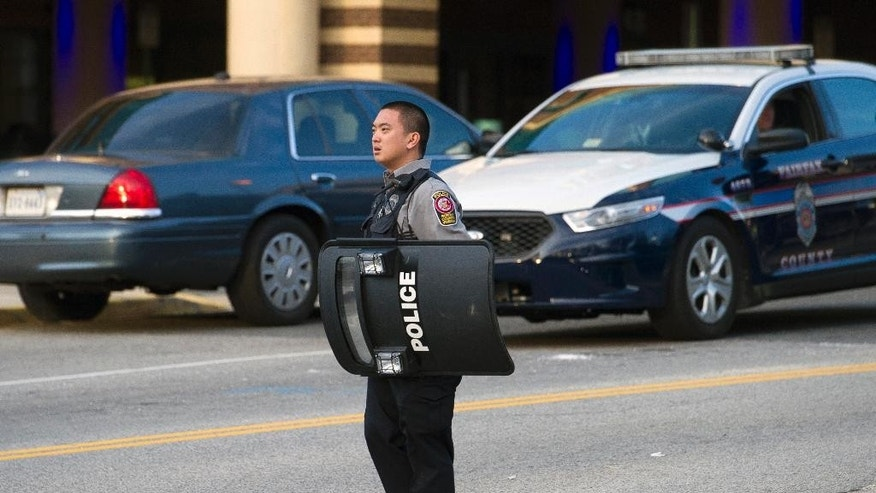 A Fairfax County, Va. Police officer holds a ballistic shield as he stands guard at Inova Fairfax Hospital Center in Falls Church, Va., Tuesday, March 31, 2015, where a prisoner broke free from his security guard and took his gun. One shot was fired early Tuesday as a guard wrestled with a prisoner, who then fled a northern Virginia hospital with a gun setting off a lockdown and search, police said. (AP Photo/Cliff Owen)