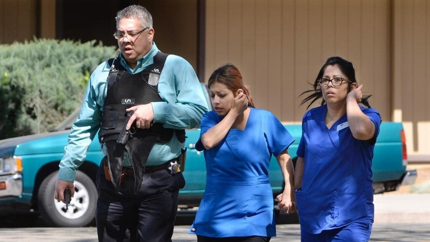 Medical personnel are evacuated by a Fresno Police officer at the scene of a shooting at a medical clinic Tuesday, March 31, 2015, in Fresno, Calif. A man and a woman were found dead after a shooting at the clinic in downtown Fresno, police in central California said. (AP Photo/The Fresno Bee, John Walker)