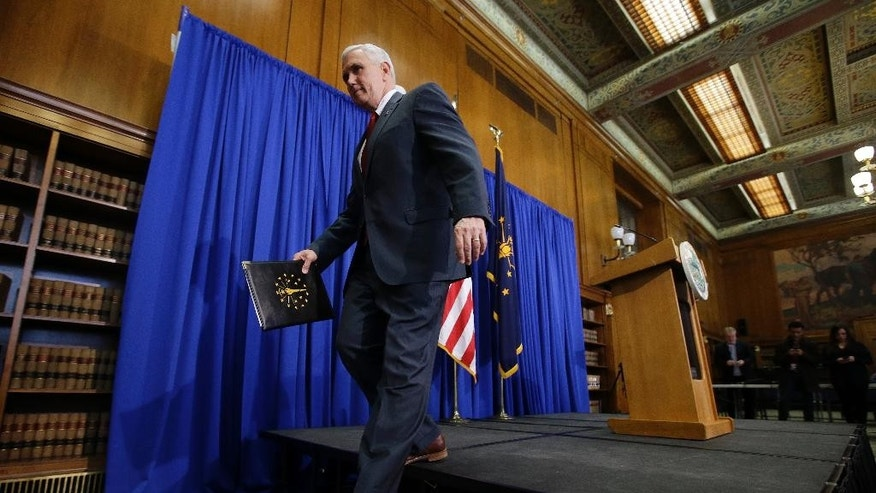 Indiana Gov. Mike Pence steps off the podium after a news conference discussing the state's new religious-freedom law, Tuesday, March 31, 2015, in Indianapolis. Pence said that he wants legislation on his desk by the end of the week to clarify that the state's new religious-freedom law does not allow discrimination against gays and lesbians. (AP Photo/Darron Cummings)