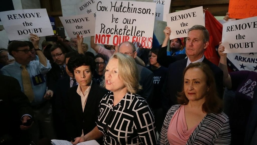 Tippi McCulloch, center, surrounded by opponents of a religious objection measure passed by the Arkansas House the day before, speaks outside the governor's office, Wednesday, April 1, 2015, at the state Capitol in Little Rock, Ark. Arkansas Gov. Asa Hutchinson on Wednesday called for changes to a religious objection measure facing a backlash from businesses and gay rights groups, saying it wasn't intended to sanction discrimination based on sexual orientation. (AP Photo/Danny Johnston)