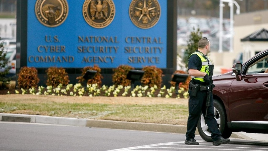 A police officer directs a vehicle to turn away at the National Security Agency, Monday, March 30, 2015, in Fort Meade, Md. Earlier, a firefight erupted when two men dressed as women tried to ram a car into a gate, killing one of them and wounding the other, officials said. (AP Photo/Andrew Harnik)