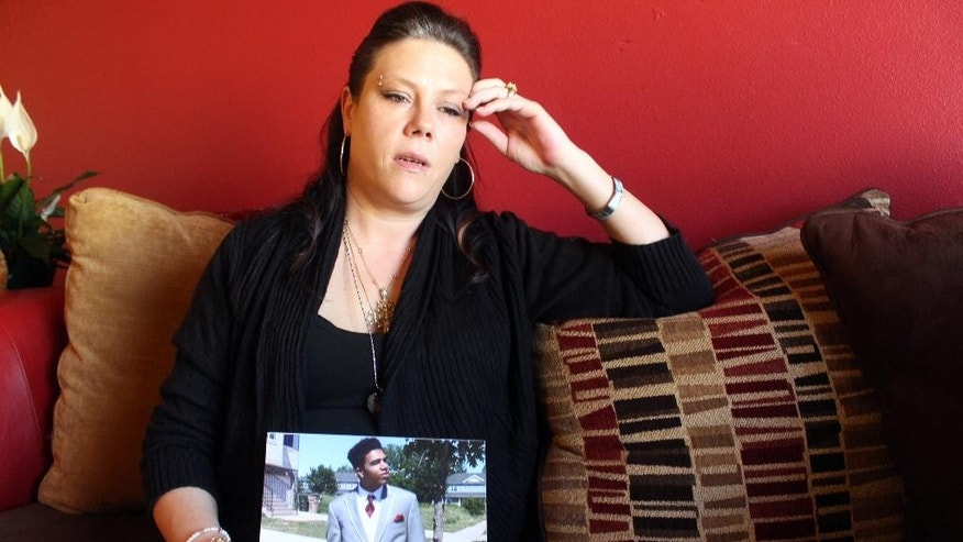 Andrea Irwin holds a photo of her son Tony Robinson Tuesday, April 1, 2015 in Madison, Wis. Irwin, whose biracial son died at the hands of a white Madison Wisconsin police officer in March, says she trusts prosecutors will get to the truth of what really happened.  (AP Photo/Carrie Antlfinger)