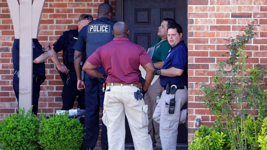April 1, 2015: Tulsa police gather at the front entrance of a home as they investigate after the bodies of four people were found in Tulsa, Okla.