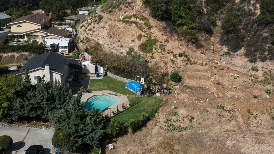A home with a swimming pool sits near hillside, Thursday April 2, 2015, in Altadena, Calif. California Gov Jerry Brown on Wednesday, April 1, ordered a mandatory 25 percent overall cutback in water use by cities and towns, but not farms, in the most sweeping drought measure in history by the United States' largest state economy. The water crackdown comes as California moves toward its fourth summer of drought after record low winter snowfall, leaving the state with a year's worth of water stored in its reservoirs, and dwindling groundwater for wells. (AP Photo/Ringo H.W. Chiu)