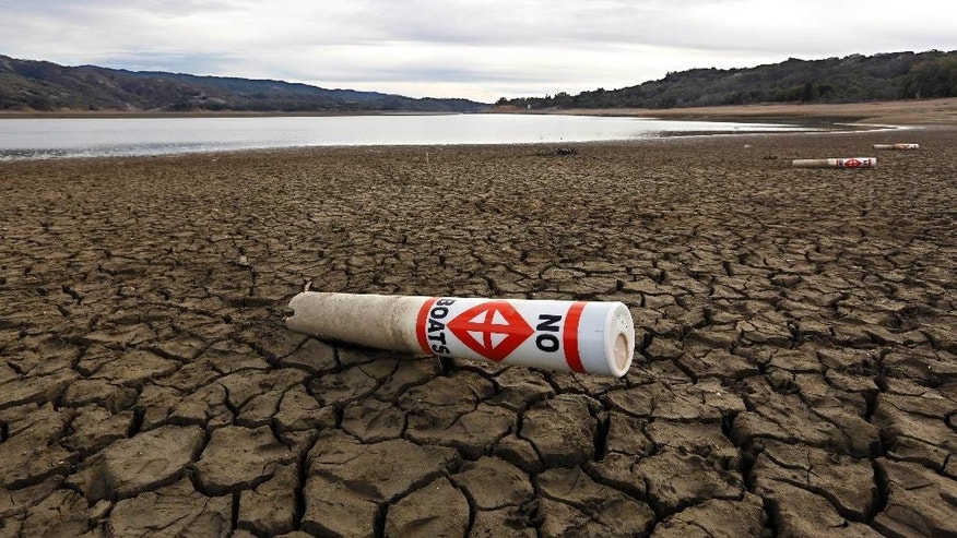 FILE - In this Feb. 4 2014 file photo, a warning buoy sits on the dry, cracked bed of Lake Mendocino near Ukiah, Calif. On Wednesday, April 1, 2015, California Gov. Jerry Brown ordered the first mandatory, statewide water cutbacks by cities and towns as the state's nearly 40 million people head into a fourth summer of severe drought. Under the order the state can fine water agencies $10,000 a day if they fail to meet state targets for water conservation. The California Energy Commission will help oversee financial rewards for Californians who buy water-saving toilets and other appliances. And Brown's order mandates that water agencies look at changing rates to encourage saving water. (AP Photo/Rich Pedroncelli, File)