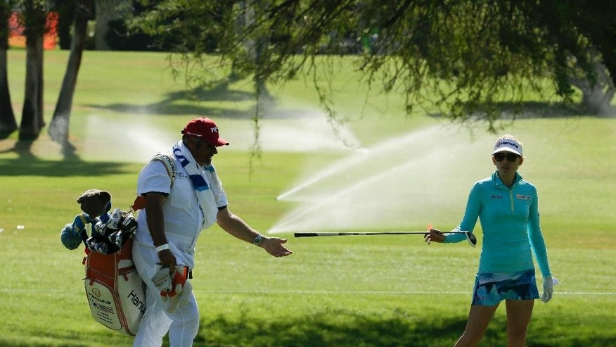 Sydnee Michaels, right, hands off a club to her caddie on the 11th hole as the rough gets watered during the first round of the LPGA Tour ANA Inspiration golf tournament at Mission Hills Country Club on Thursday, April 2, 2015 in Rancho Mirage, Calif. California Gov. Jerry Brown ordered officials Wednesday to impose statewide mandatory water restrictions for the first time in history as surveyors found the lowest snow level in the Sierra Nevada snowpack in 65 years of record-keeping. (AP Photo/Chris Carlson)