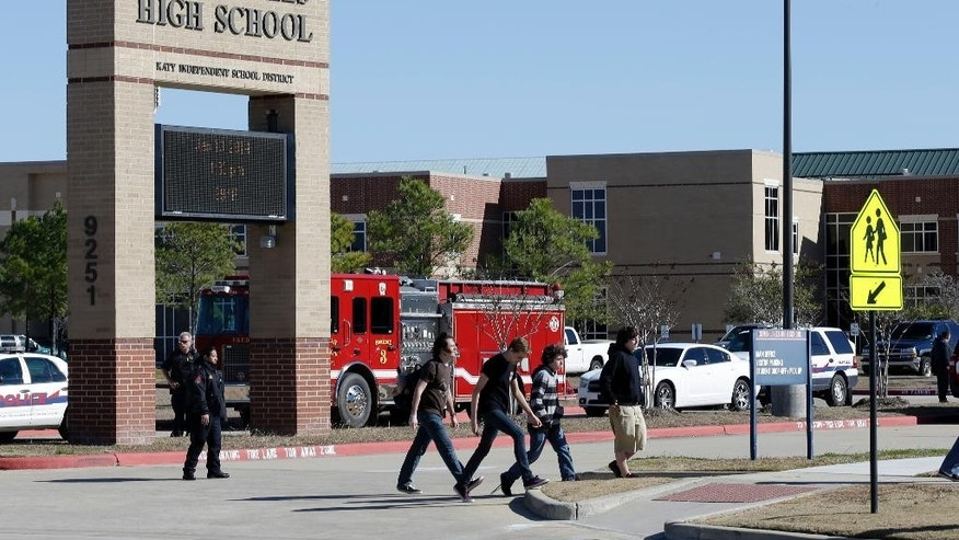 FILE - In this Jan. 13, 2014 file photo, students pass by Seven Lakes High School after being evacuated and released from school for the day after a bomb squad was called to the school after a potentially explosive device was found. Threats against schools don't just come written on bathroom walls these days. Spread using smart phone apps, social media and Internet phone services, anonymous reports of bombs or other threats of violence are forcing school evacuations and a response by police swat teams or other authorities to what in the vast majority of cases turns out to be a hoax. (AP Photo/Pat Sullivan, File)