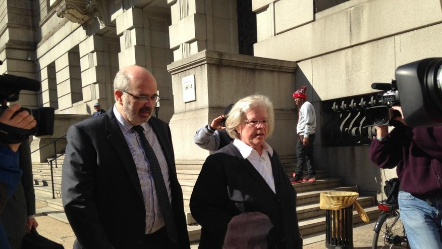 Episcopal Bishop Heather Cook leaves Baltimore City Circuit Court after her arraignment, with attorney Jose Moline, left, Thursday, April 2, 2015 in Baltimore. Cook faces vehicular manslaughter, drunken driving and distracted driving charges stemming from a Dec. 27 accident when she fatally struck 41-year-old Tom Palermo on his bicycle. Cook entered a not-guilty plea, and a June 4th trial date has been set. (AP Photo/Juliet Linderman)