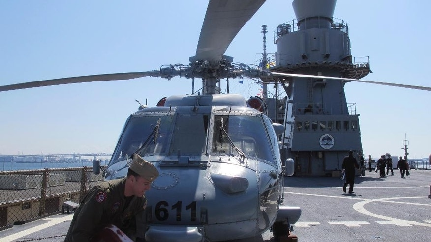 In this March 31, 2015 photo, helicopter crew members secure their aircraft to the deck of the USS Blue Ridge, flagship of the U.S. Seventh Fleet, during a port call at Yokohama, near Tokyo. U.S. and Japanese military officers say they hope new defense guidelines may soon free up the Japanese navy to play a more active role in the Pacific and beyond, plying some of the world's most hotly contested waters. (AP Photo/Eric Talmadge)
