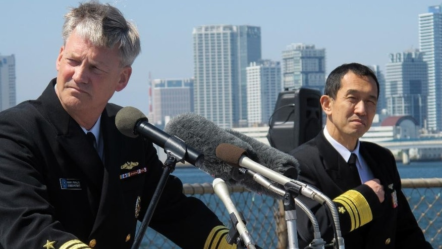 In this March 31, 2015 photo, Vice Adm. Robert Thomas, left, commander of the U.S. Seventh Fleet, and Vice Adm. Eiichi Funada, commander of the Japanese fleet, address the media at a news conference on the deck of the USS Blue Ridge during a port call at Yokohama, near Tokyo. U.S. and Japanese military leaders say they hope new defense guidelines may soon free up the Japanese navy to play a more active role in the Pacific and beyond. (AP Photo/Eric Talmadge)