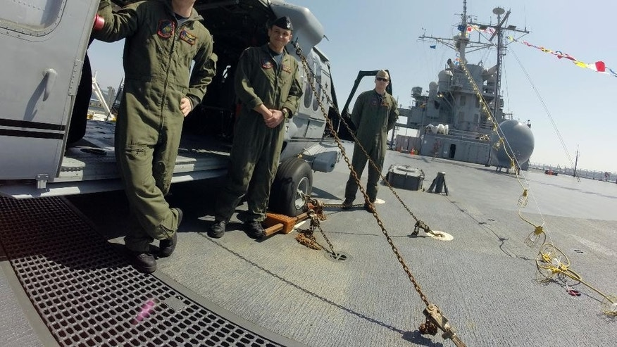 """In this March 31, 2015 photo, crewmembers of the """"Golden Falcons"""" helicopter squadron aboard the USS Blue Ridge take a break beside their aircraft during a port call in Yokohama, near Tokyo. Even as Japan remains divided over proposed changes in the role Tokyo should play in regional security issues, senior U.S. and Japanese military officers say they hope the Japanese navy may soon be freed up to play a more active role in the Pacific and beyond. (AP Photo/Eric Talmadge)"""