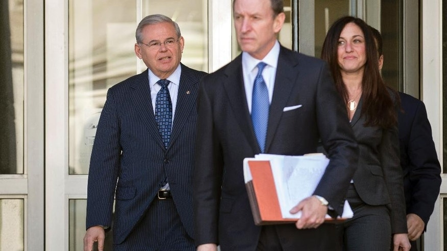 U.S. Sen. Bob Menendez, left, leaves federal court, Thursday, April 2, 2015, in Newark, N.J. Menendez, the top Democrat on the U.S. Senate Foreign Relations Committee, was indicted on corruption charges, accused of using his office to improperly benefit an eye doctor and political donor. (AP Photo/John Minchillo)