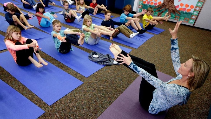 FILE - In this Dec. 11, 2012 file photo, Yoga instructor Kristen McCloskey, right, leads a class of third graders at Olivenhain Pioneer Elementary School in Encinitas, Calif. A California appeals court says yoga taught in San Diego County schools doesn't violate religious freedom. (AP Photo/Gregory Bull,File)