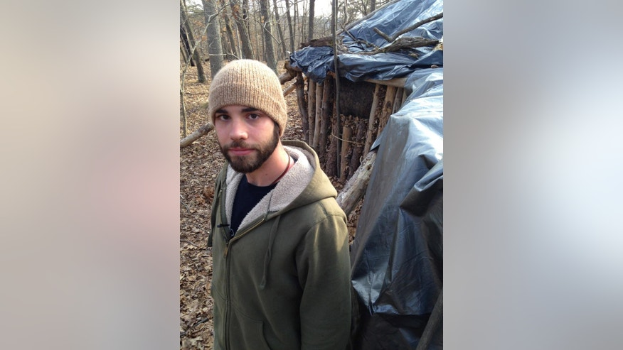In this March 23, 2015 photo, Dylan Miller, a senior at Juniata College, poses in front of his shelter in the woods near campus in Huntingdon, Pa. For his senior research project on simple living, Miller decided to emulate Thoreau instead of just reading his work. So, deep in the woods about a half-hour's walk from campus, he built a hut out of fallen trees, leaves and a tarp - unheated, no plumbing - and has been living there since the beginning of the school year, studying by lantern and chasing away the occasional bear. (AP Photo/Michael Rubinkam)