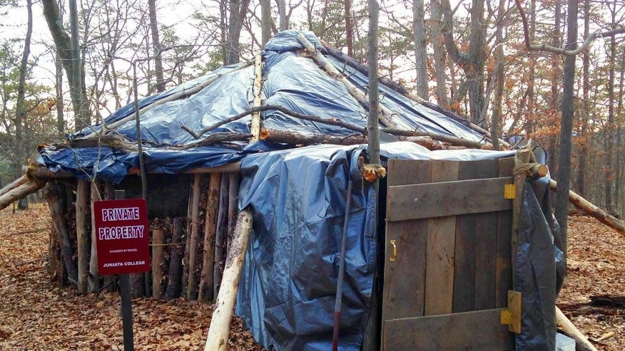 This March 23, 2015 photo shows the hut that Juniata College senior Dylan Miller built in the woods near campus in Huntingdon, Pa. For his senior research project on simple living, Miller decided to emulate Thoreau instead of just reading his work. So, deep in the woods about a half-hour's walk from campus, he built a hut out of fallen trees, leaves and a tarp - unheated, no plumbing - and has been living there since the beginning of the school year, studying by lantern and chasing away the occasional bear. (AP Photo/Michael Rubinkam)