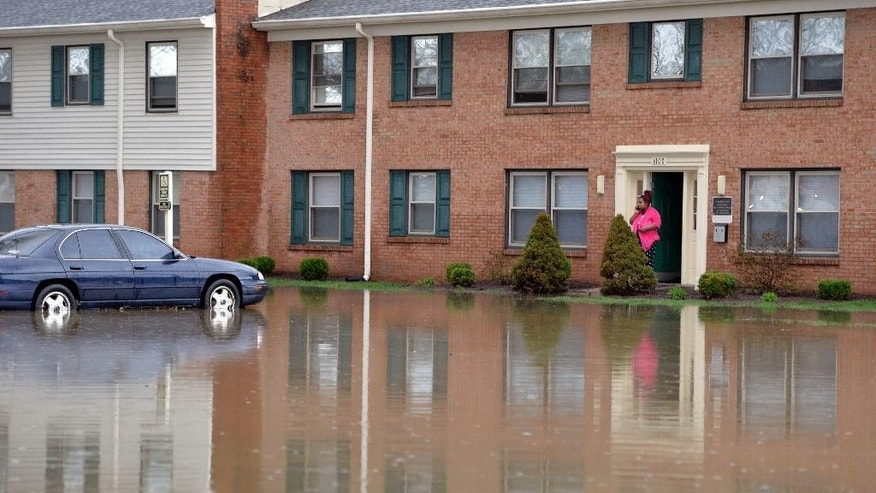 Simone Wester talks with family on the phone from the front door of her apartment building at the Guardian Court Apartments in Louisville, Ky., Friday, April 3, 2015. More than a foot of water flooded the apartment complex. Authorities in Louisville, Kentucky, made more than 100 water rescues early Friday as area storms flooded roads and prompted at least one evacuation. (AP Photo/Timothy D. Easley)