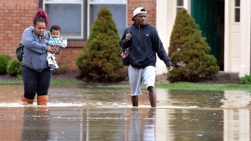 Kevin Mansfield, right, helps Simone Wester and her 7-month old son Jeremiah from her flooded apartment building at the Guardian Court Apartments in Louisville, Ky., Friday, April 3, 2015.  Authorities made more than 100 water rescues early Friday as area storms flooded roads and prompted at least one evacuation. (AP Photo/Timothy D. Easley)