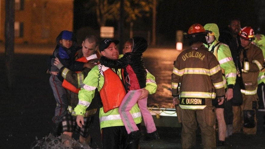 Rescue crews help residents at the Guardian Court Apartments evacuate after flooding in the area on Friday, April 3, 2015 in Louisville, Ky.   Authorities in Louisville made more than 100 water rescues early Friday as area storms flooded roads and prompted at least one evacuation.  (AP Photo/The Courier-Journal, Michael Clevenger) NO SALES; MAGS OUT; NO ARCHIVE; MANDATORY CREDIT