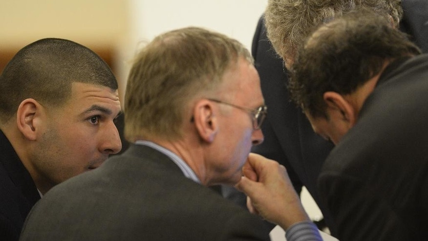 Former New England Patriots football player, left,  talks with his attorneys during his murder trial at the Bristol County Superior Court in Fall River, Mass., on Friday, April 3, 2015. Hernandez is charged with killing Odin Lloyd.  (AP Photo/CJ Gunther, Pool)