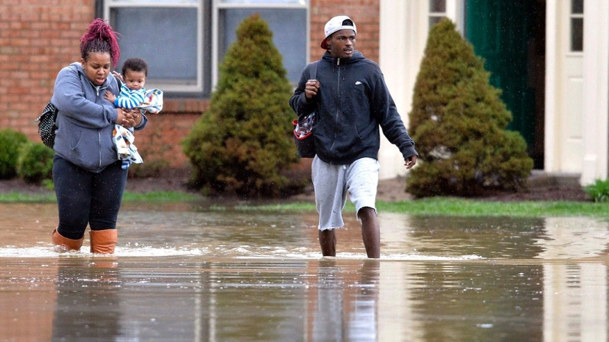 April 3, 2015: Kevin Mansfield, right, helps Simone Wester and her 7-month old son Jeremiah from her flooded apartment building at the Guardian Court Apartments in Louisville, Ky.