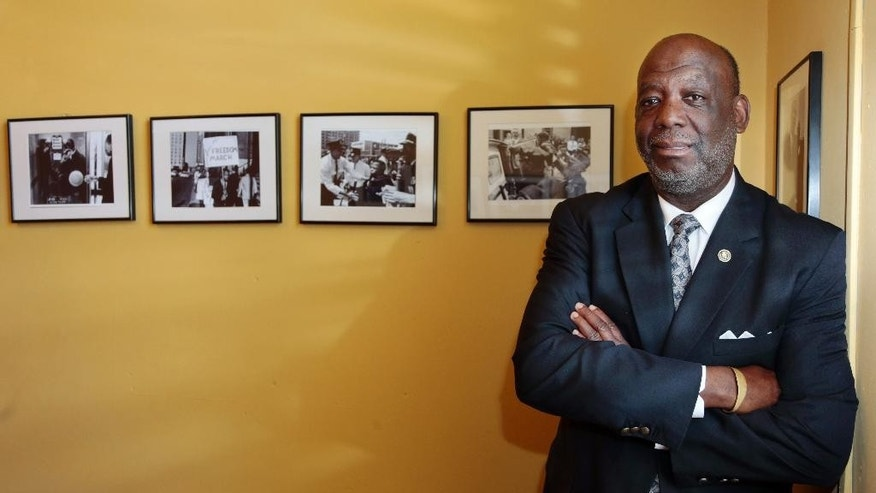 In this April 1, 2015, photo, American Baptist College President Forrest E. Harris poses with photos from the civil rights movement in his Nashville, Tenn. office. Some pastors affiliated with the small Baptist seminary have threatened to withdraw financial support after a lesbian bishop was invited to speak at the college as part of a lecture series. (AP Photo/Mark Humphrey)