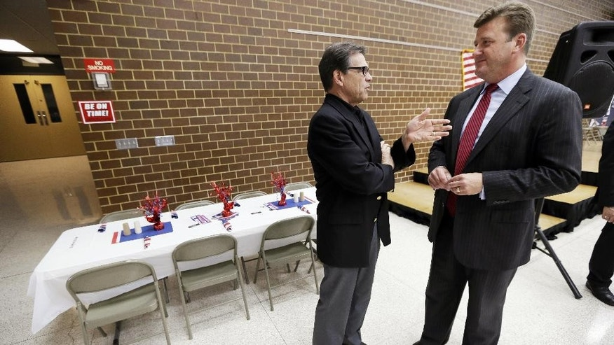 FILE - In this July 19, 2014 file photo, then-Texas Gov. Rick Perry, left, talks with Story City pastor Jamie Johnson, who is now working for Perry, during a meeting with local party activists in Algona, Iowa. Iowa pastors have been politically active for many years and going into 2016, a host of potential candidates are wooing pastors. (AP Photo/Charlie Neibergall)