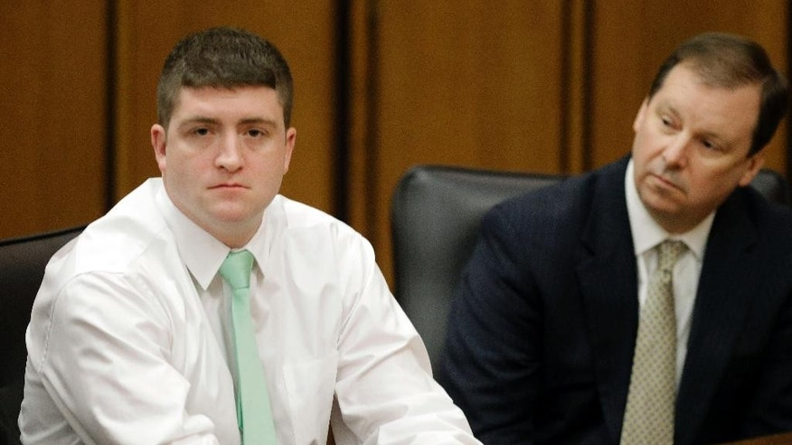 FILE - In this March 13, 2015 file photo, suspended Cleveland Police patrolman Michael Brelo, left, sits with attorney Tom Shaughnessy during an administrative hearing in Cleveland. Brelo faces two voluntary manslaughter charges in the shooting deaths of Timothy Russell and Malissa Williams following a high-speed chase in November 2012. His trial is scheduled to begin Monday, April 6, 2015 in Cleveland. (AP Photo/Mark Duncan, File)