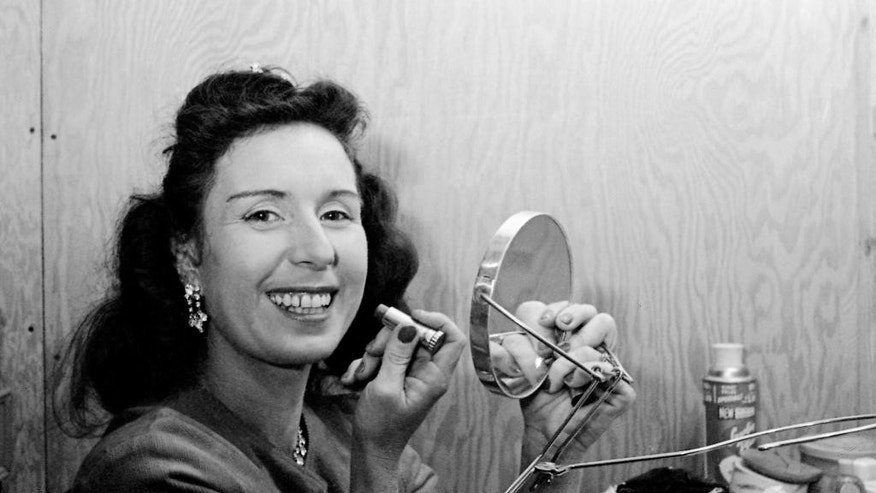 FILE - In this Jan. 24, 1964 file photo, Jenny Wallenda, a member of the famous Wallenda high wire act, applies makeup in a dressing room prior to appearing at opening of the Shrine Circus in Detroit. Wallenda, the matriarch of the famous family of high-flying circus performers, died late Saturday, April 4, 2015, at her home in Sarasota, Fla., according to family members. She was 87. (AP Photo/Alvan Quinn, File)