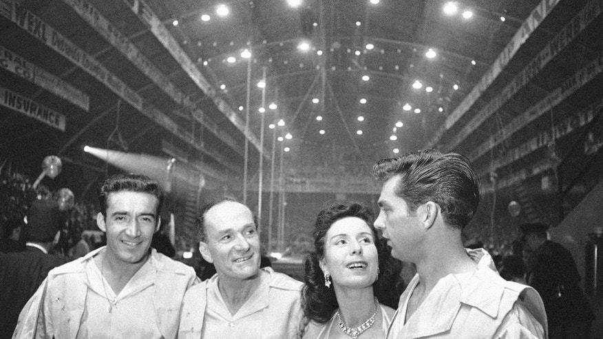 FILE - In this Jan. 24, 1964 file photo, Karl Wallenda, center left, and his daughter Jenny, center right, wait on sideline with troupe members Louis Murillo, left, and Andy Anderson, before performing a high wire act at the opening of the Shrine Circus in Detroit. Jenny Wallenda, the matriarch of the famous family of high-flying circus performers, died late Saturday, April 4, 2015, at her home in Sarasota, Fla., according to family members. She was 87. (AP Photo/Alvan Quinn, File)