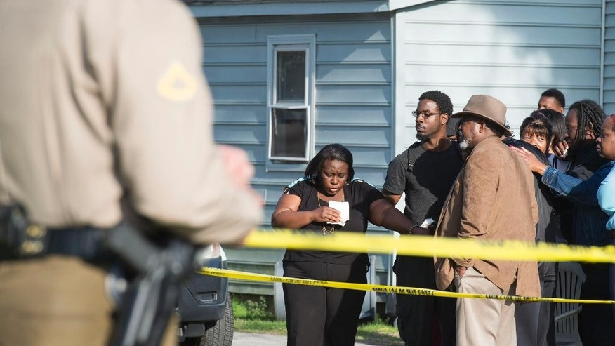 Onlookers gather outside of a house, where police say seven children and one adult have been found dead Monday, April 6, 2015, in Princess Anne, Md. Officers were sent to the home Monday after being contacted by a concerned co-worker of the adult. (AP Photo/The Daily Times, Joe Lamberti)