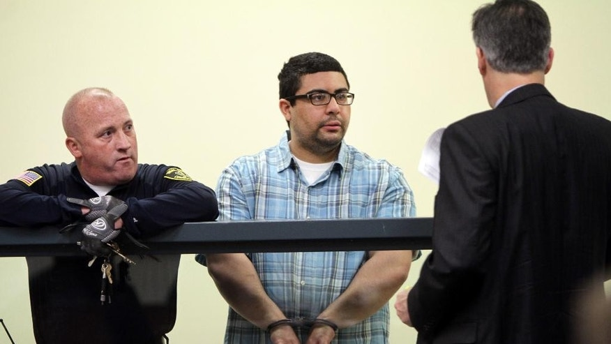 April 6, 2015: Carlos Colina, center, speaks with his attorney John Cunha, Jr., right, during his arraignment in Cambridge District Court in Medford, Mass.