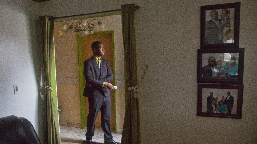 Harold Ekeh, a senior at Elmont Memorial High School, stands in the foyer of his home as he waits to do an interview, Tuesday, April 7, 2015, in New York. Ekeh has been accepted to all 13 colleges he applied to, including the eight Ivy League schools. Ekeh, who plans to study medicine, has until May 1 to decide where he'll go. (AP Photo/Bebeto Matthews)