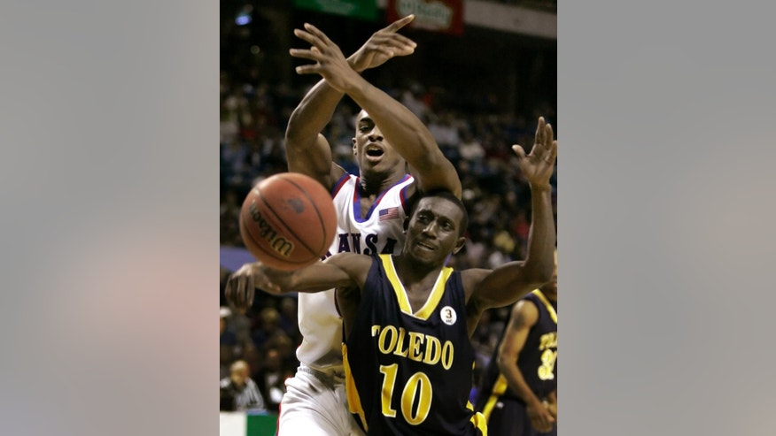 FILE - In this Dec. 9, 2006, file photo, Kansas forward Darrell Arthur, back, and Toledo guard Kashif Payne (10) chase after a loose ball during an NCAA college basketball game in Kansas City, Mo. Payne is one of six former Toledo basketball and football players who were accused Wednesday, May 6, 2009, of taking part in a point-shaving scheme by either affecting the outcomes in game or giving information to two businessmen so they could place wagers on the games.  A judge on Tuesday, April 7, 2015, gives the last sentences to 2 of 7 former University of Toledo players who altered their play or fed info to gamblers in a point-shaving scandal a decade ago. The gamblers will be sentenced in May. (AP Photo/Charlie Riedel, File)