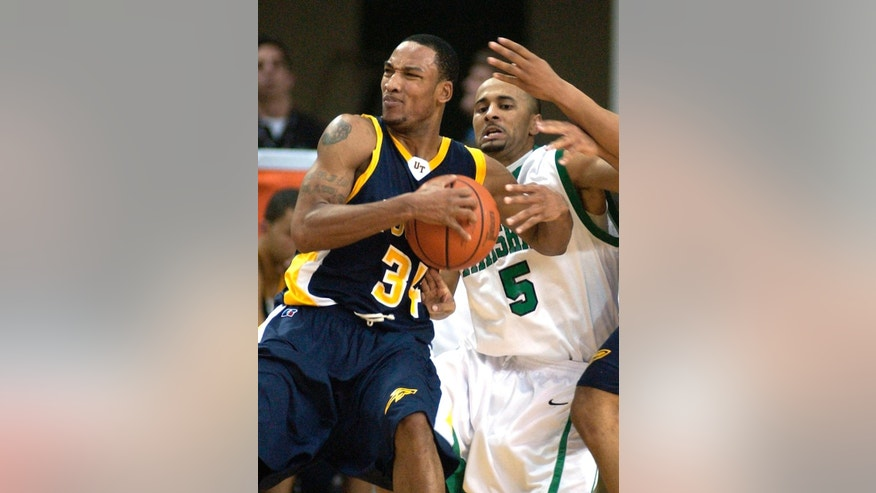 FILE - In this Jan. 15, 2005, file photo, Marshall's Enoch Bunch, center, guards Toledo's Keith Triplett during an NCAA college basketball game in Huntington, W.Va. Triplett is one of six former Toledo basketball and football players who took part in a point-shaving scheme by either affecting the outcomes in game or giving information to two businessmen so they could place wagers on the games. A judge on Tuesday, April 7, 2015, gives the last sentences to 2 of 7 former University of Toledo players who altered their play or fed info to gamblers in a point-shaving scandal a decade ago. The gamblers will be sentenced in May. (AP Photo/Randy Snyder, File)