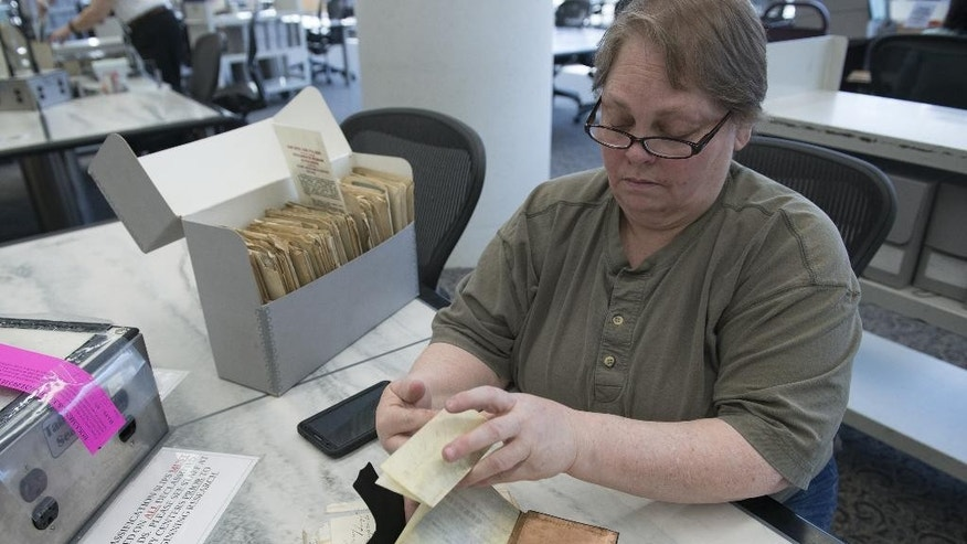 "In this Monday, April 6, 2015 photo, Karen Needles looks through pardon case files from the Lincoln administration at the National Archives in College Park, Md. ""They call me Lady Lincoln,"" chuckles the former middle school history teacher who digitally scans every original record she can from Lincoln's administration — from letters he signed to his final paycheck for $1,981.67 — posting them online for anyone to see without charge. (AP Photo/Molly Riley)"