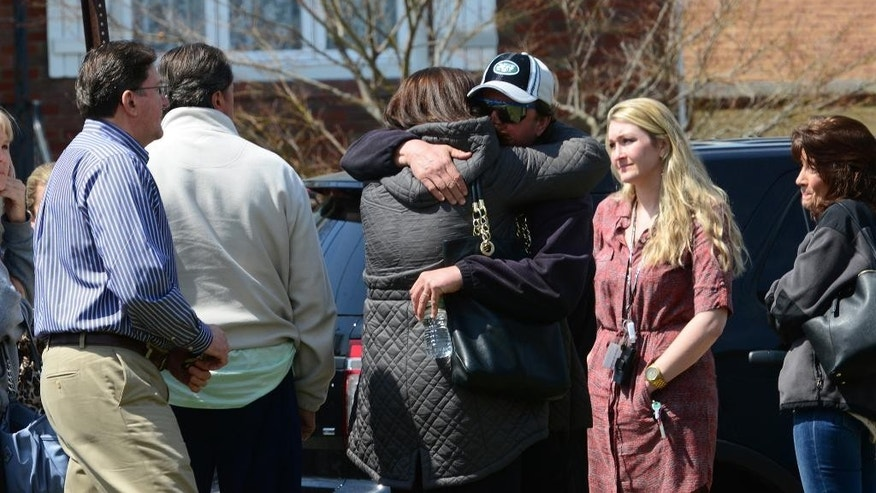 People gather across the street from the home where the bodies of an elderly couple were found on Monday, April 6, 2015 in Elmwood Park, N.J. Prosecutors say Michael Juskin, a 100-year-old man, apparently killed his 88-year-old wife, Rosalia with an ax as she slept in their home, then killed himself in the bathroom with a knife. But it's still not clear what sparked the murder-suicide late Sunday in Elmwood Park. (AP Photo/Northjersey.com, Tariq Zehawi)  MANDATORY CREDIT