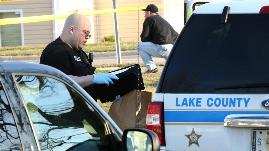 A Lake County Major Crimes Task Force Investigator holds an evidence bag on Saturday, April 4, 2015, in Zion, Ill., after a Zion Police officer was involved in a fatal shooting. An autopsy has revealed that a teenager who was killed by police in Illinois over the weekend was shot twice in the back. (AP Photo/The Chicago Tribune, Joe Shuman)