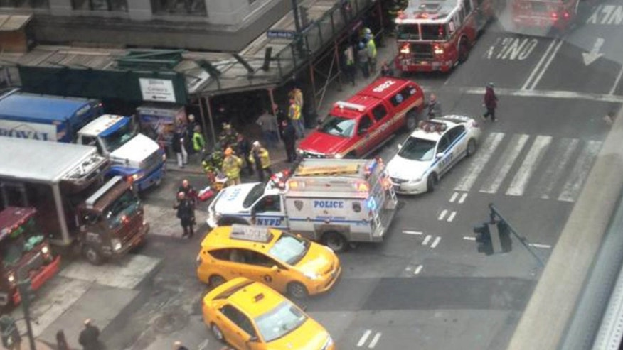 In this photo provided by Kaitlyn Ford, emergency personnel work the scene where authorities said four construction workers suffered serious injuries in a partial wall collapse inside a commercial building near Grand Central Terminal, in New York.