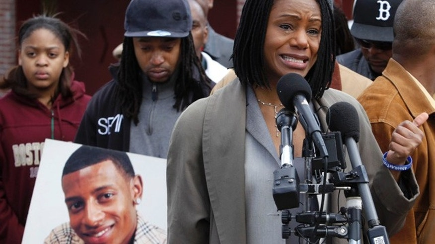 FILE - In this April 21, 2011, file photo, Thulani DeMarsay, right, of Boston, aunt of college football player Danroy Henry Jr., who was shot and killed by a police officer, speaks to reporters as Danroy's uncle Jamele Dozier, also of Boston, holds a photograph of him during a news conference, in Boston's Roxbury neighborhood. (AP Photo/Steven Senne, File)