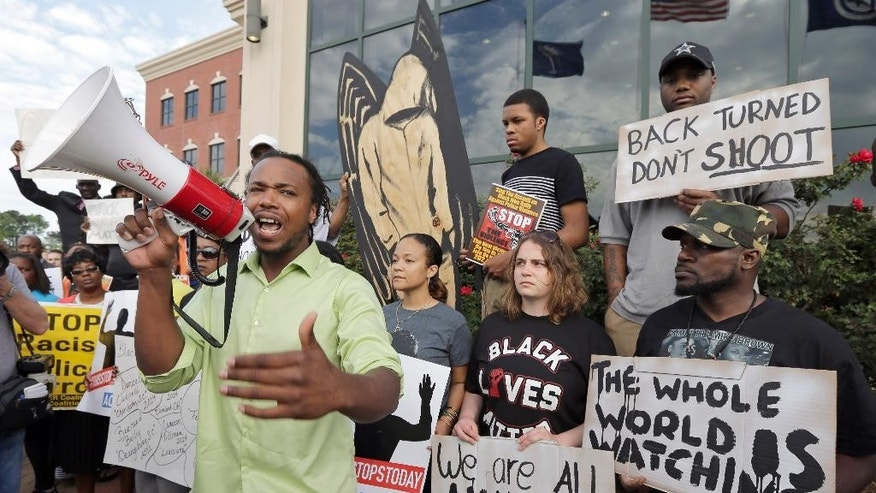 Muhiydin D'Baha leads a group protesting the shooting death of Walter Scott at city hall in North Charleston, S.C., Wednesday, April 8, 2015.  Scott was killed by a North Charleston police office after a traffic stop on Saturday. The officer, Michael Thomas Slager,  has been charged with murder. (AP Photo/Chuck Burton)