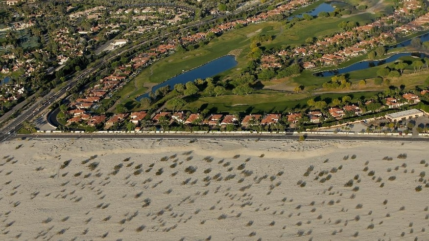 This April 3, 2015, aerial photo shows golf course communities bordering the desert in Cathedral City, Calif. California cities face mandatory targets to slash water use as much as 35 percent while regulators warn voluntary conservation hasn't been enough in the face of a devastating drought. Underlining their point was data released Tuesday, April 7, showing a new low in saving water. (AP Photo/Chris Carlson)