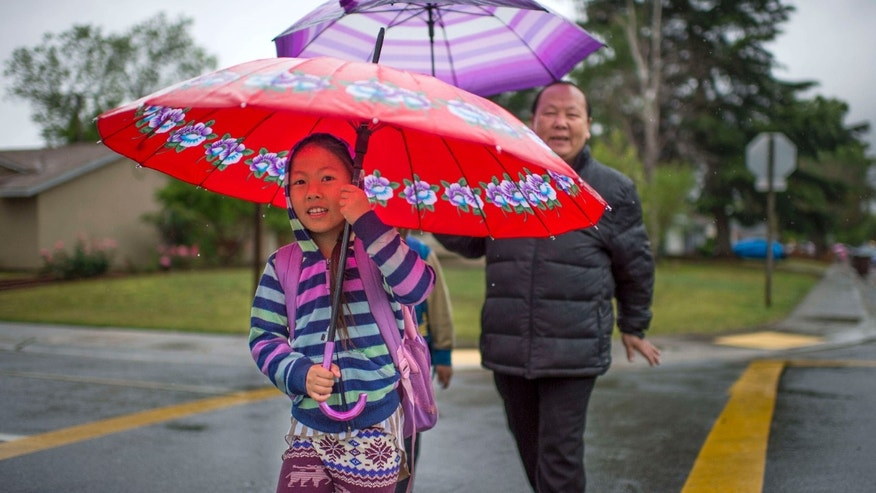 April 7, 2015: Cecilia Xiong, left, and her father, Kachang Xiong, walk to Parkway Elementary School.